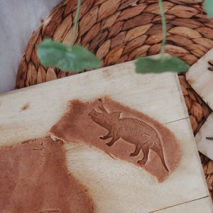 Dinosaur fossil stamped into playdough on a timber board with leaves