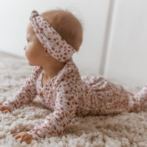 Baby laying on her tummy on fluffy rug with matching posy print top, pants and headband