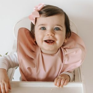 Waterproof snuggle bib in ballerina pink on a little girl in a high chair