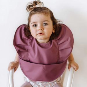 cute bib in mauve on a little girl sitting