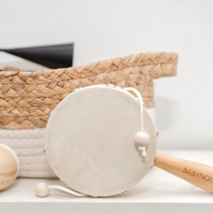 Little white tassel drum with timber handle near seagrass basket and egg shakers