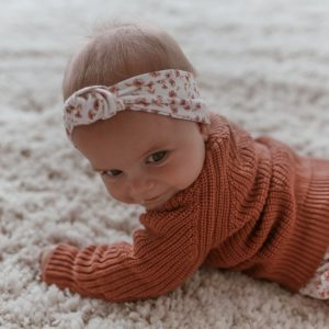 Cute little baby on woollen rug with rust coloured jumper and floral headband wrap