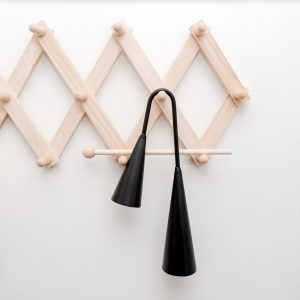 Black agogo bell hanging on timber hooks on white background