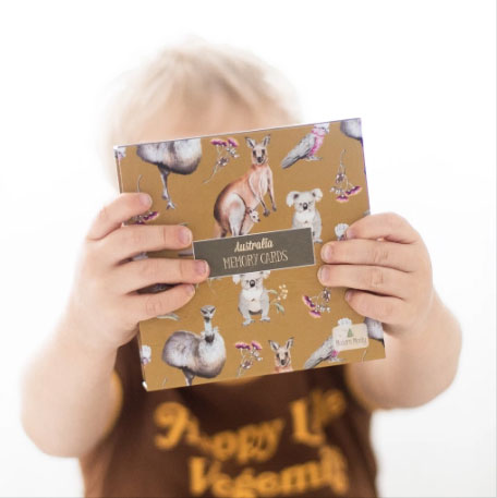 Child holding Australian themed memory card box covering his face