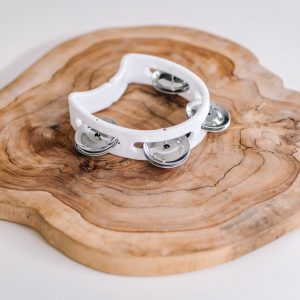 Mini white tambourine on natural timber slab and white background