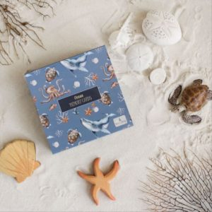 Blue box of ocean themed memory cards on white sand with shells, starfish and turtle