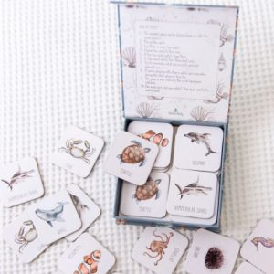Open box of ocean themed cards scattered on white bed