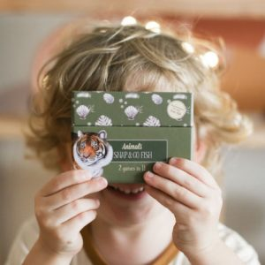 Child with curly hair holding closed boy of animal cards over his face and smiling