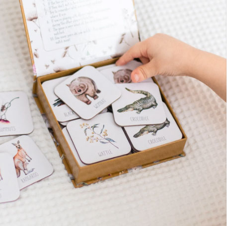Open box of Snap & Go fish on white bed with child hand picking a card up