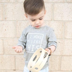 Little boy in grey jumper playing with tambourine