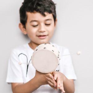 Child smiling playing with tasseldrum