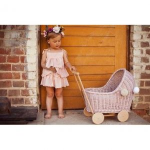 Little girl playing with wicker dolls pram in dusty pink