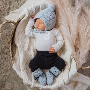 Woollen bonnet and booties in blue on a newborn baby