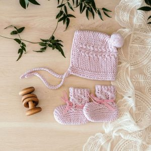 Merino bonnet and booties in blush pink laid out on timber