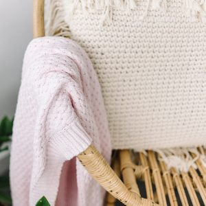 Baby blanket in blush pink hanging over chair
