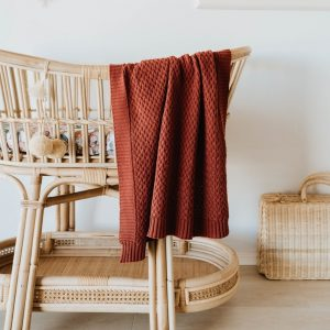 Diamond Knit baby blanket in Umber hanging over bassinet