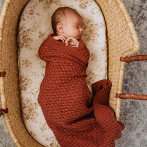 Diamond Knit umber coloured blanket wrapped around baby