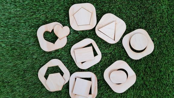 Shape matching puzzle sitting on grass with some of the shapes popped out