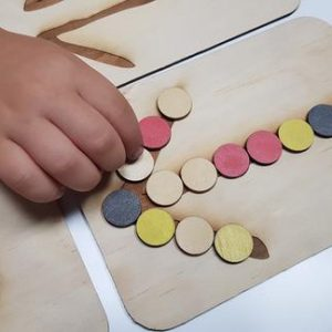 indigenous symbols tracing board with a child's hand placing a disk on