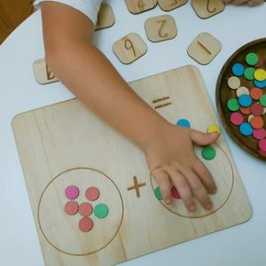 Child playing with a double sided maths board and counters.