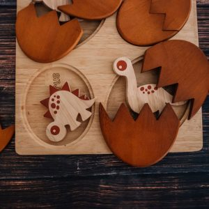 dino hatching eggs wooden puzzle with two dinosaurs popping out