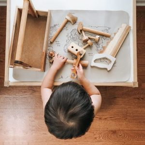 Child playing with wooden tool set pictured from above