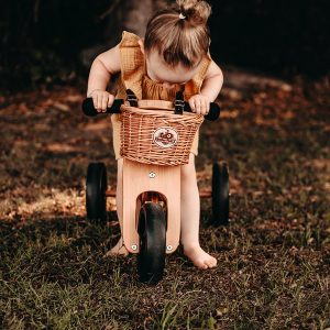 Child sitting on bike looking inside her wicker bike basket